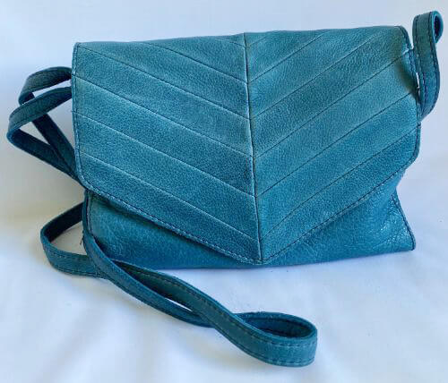 Turquoise leather shoulder bag with magnetic closure and three interior compartments
