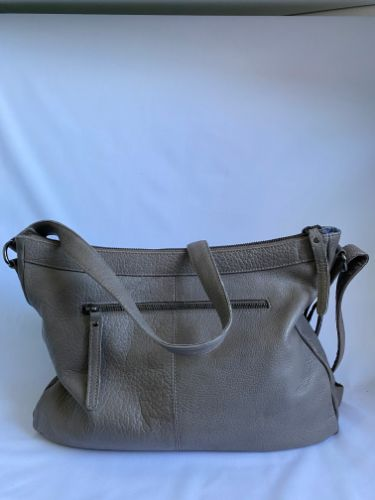 rear side of leather shoulder bag in clay colour, featuring zipped compartment
