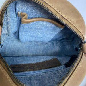 Round shoulder bag interior with denim coloured lining, zip pocket and phone pocket